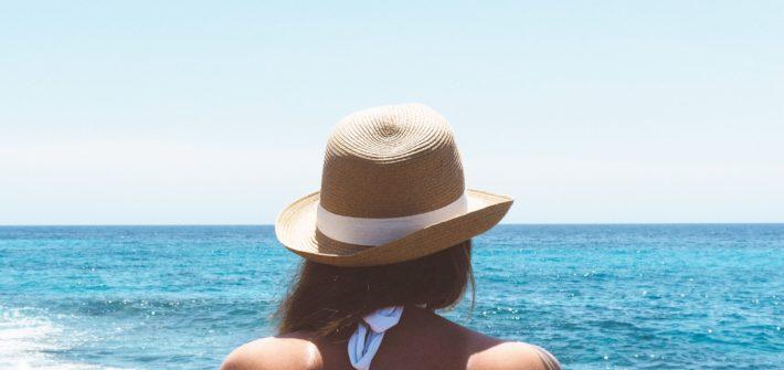 kobieta siedzi tyłem na tle morza