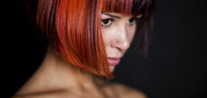 kobieta z kolorowymi włosami na ciemnym tle