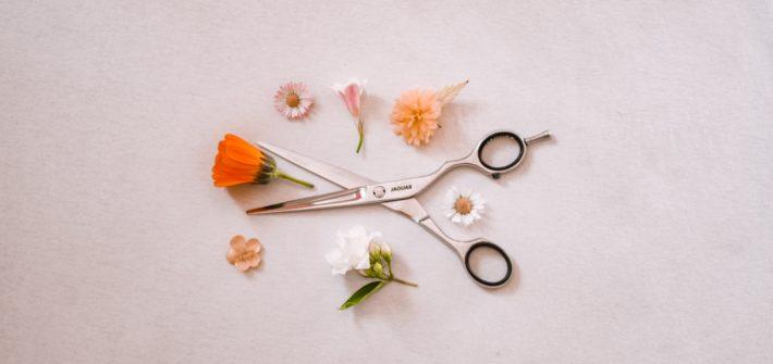 nozyczki fryzjerskie wsród kwiatków na białym tle
